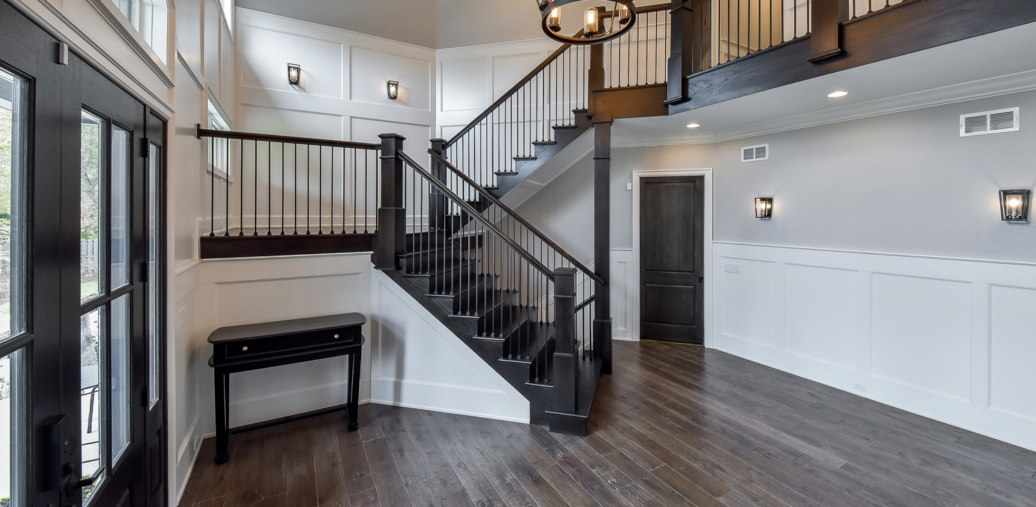 home entrance with dark wood staircase
